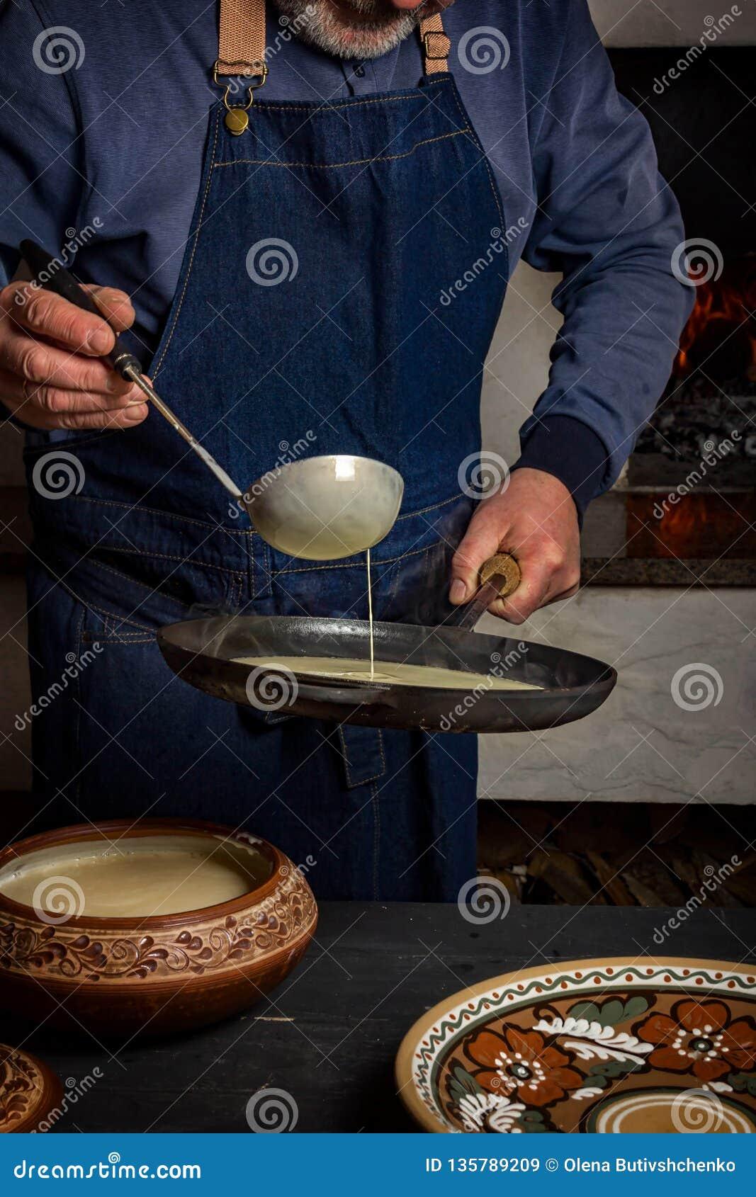 Proces gotować bliny w drewnianej kuchence Mężczyzna nalewa ciasto od kopyści w nieckę