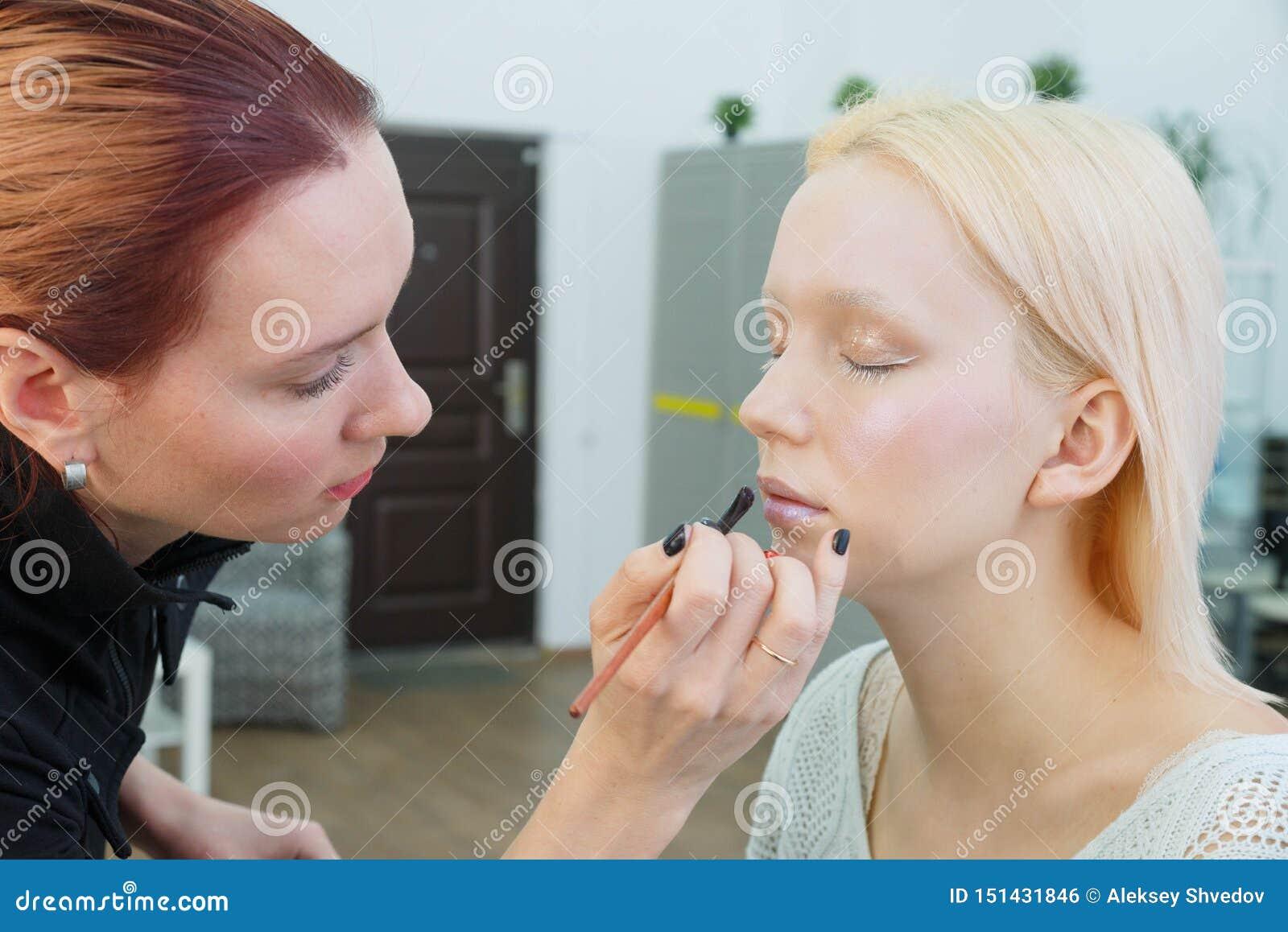 Proces om make-up te maken Grimeur die met borstel aan modelgezicht werken