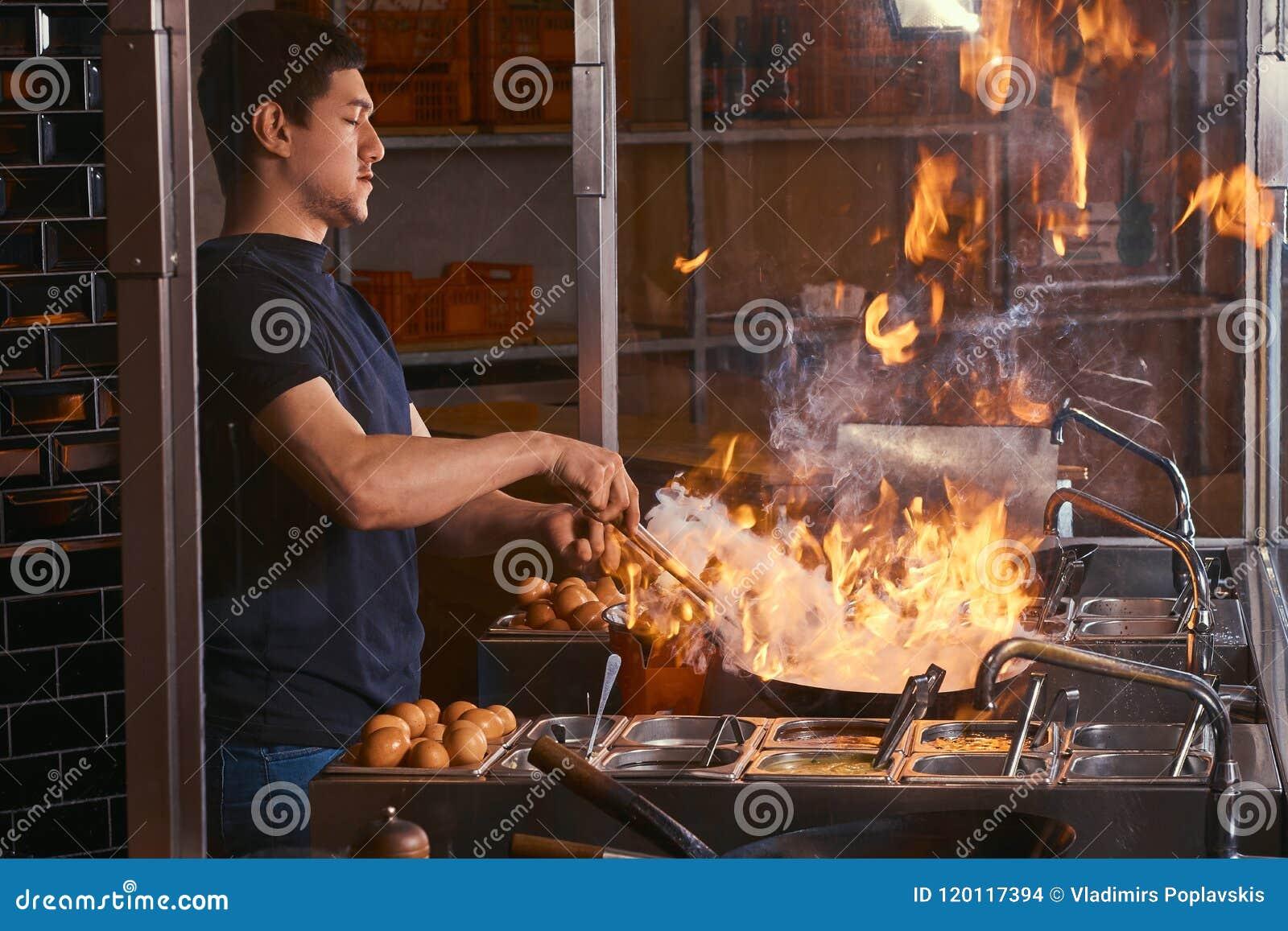 Proceso de cocinar en un restaurante asiático El cocinero es verduras de la fritada con las especias y la salsa en un wok en una