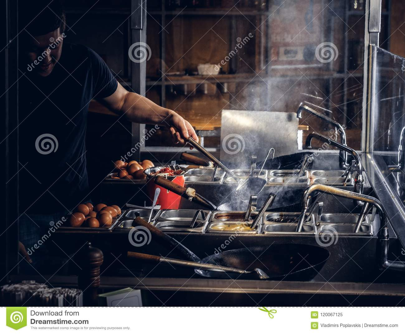 Proceso de cocinar en un restaurante asiático El cocinero está revolviendo verduras en wok