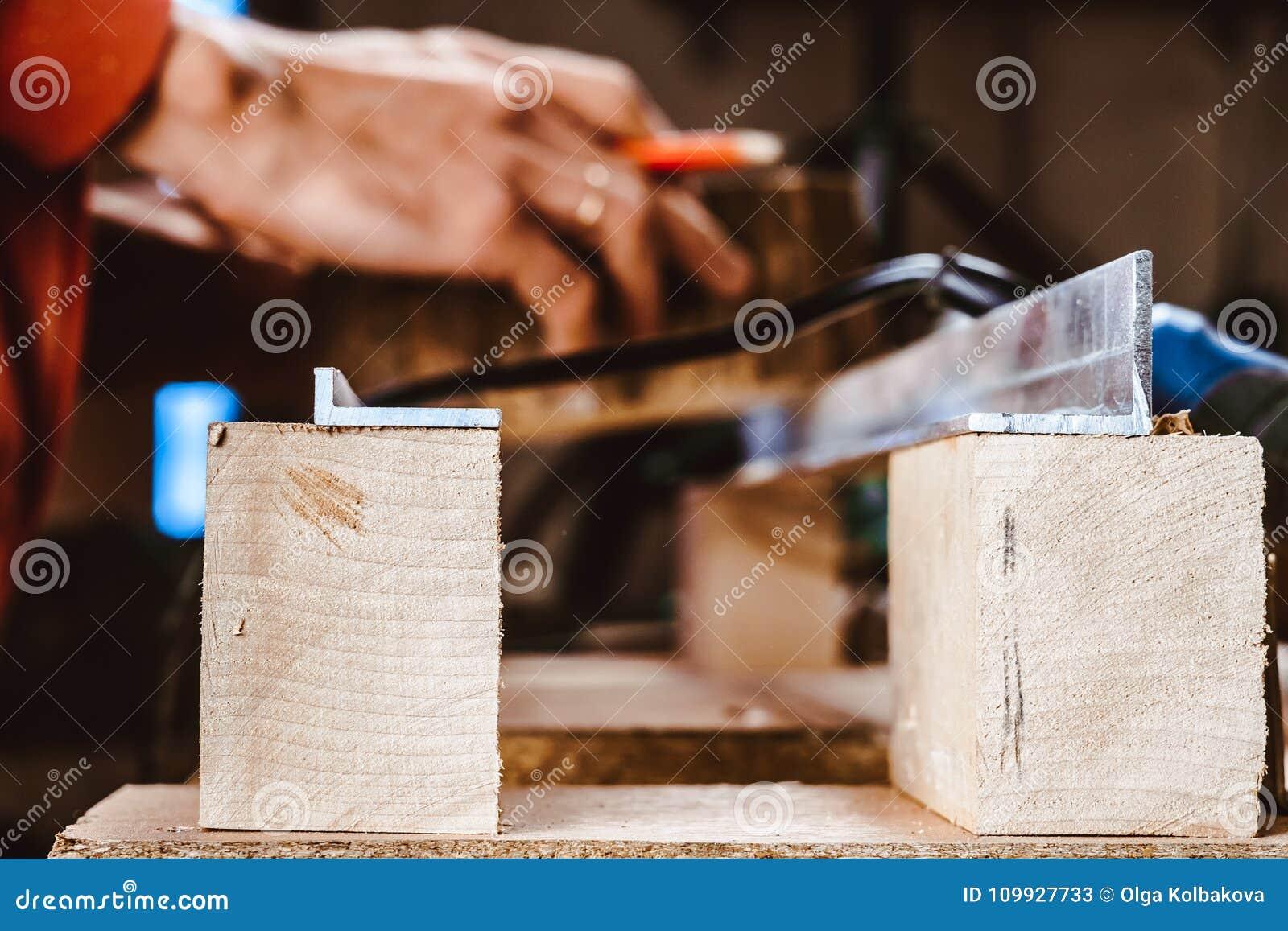 Proceso de una pieza de los muebles por una máquina para pulir un árbol la máquina de pulir en un tablero, foco selectivo