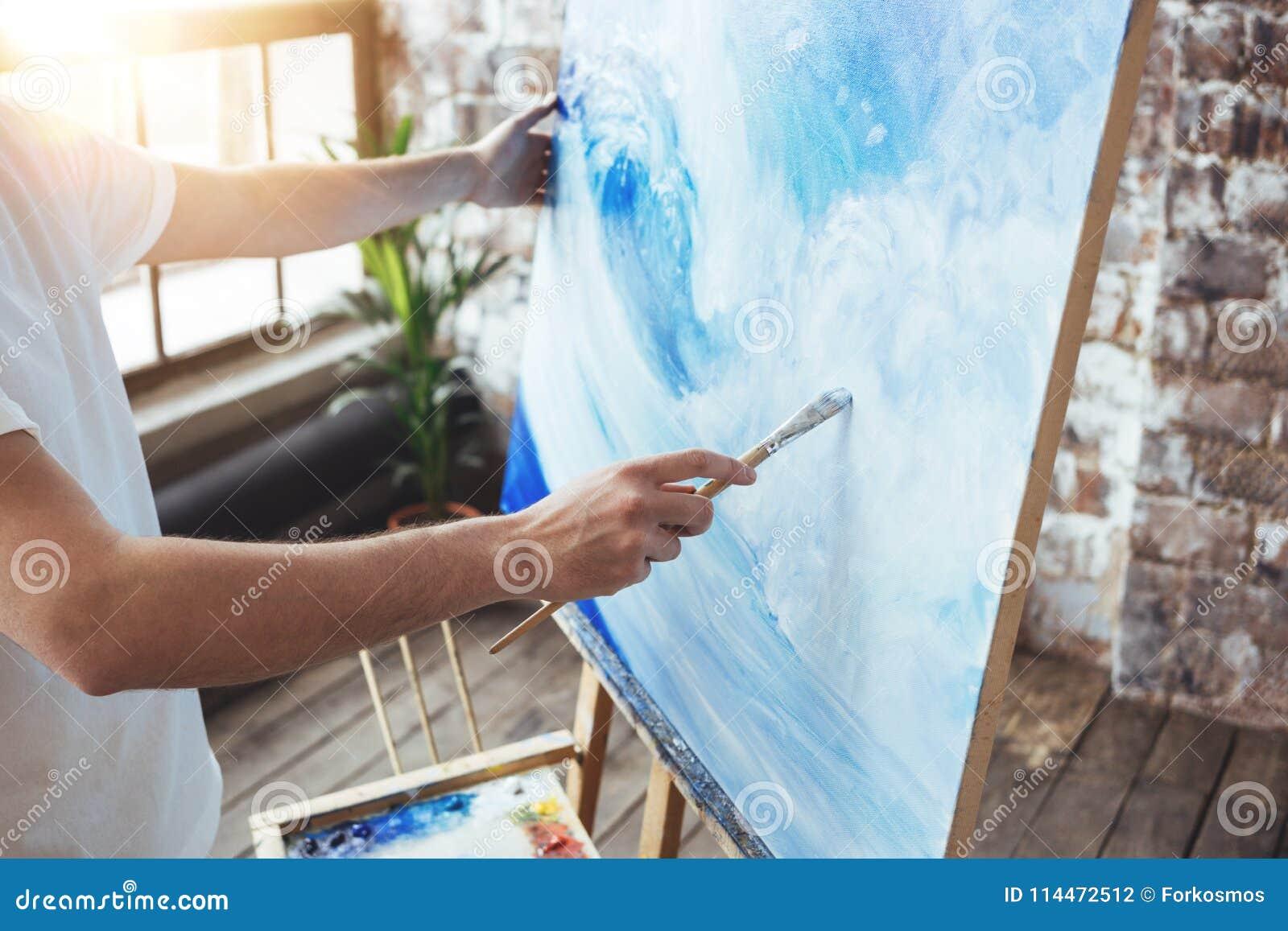 Process av att dra ett konstnärarbete i konstvindstudio med oilpaints Målarehållmålarpensel i hand framme av kanfas på staffli