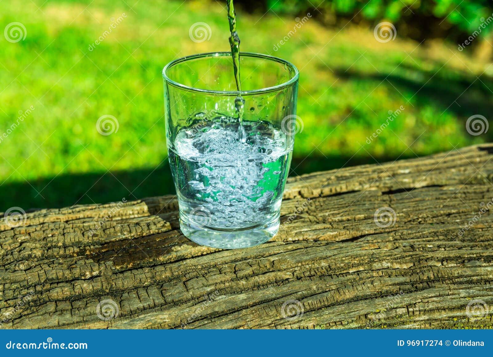 Process av att hälla rent klart vatten in i ett exponeringsglas från överkanten, träjournal, grönt gräs i bakgrunden, utomhus, hä