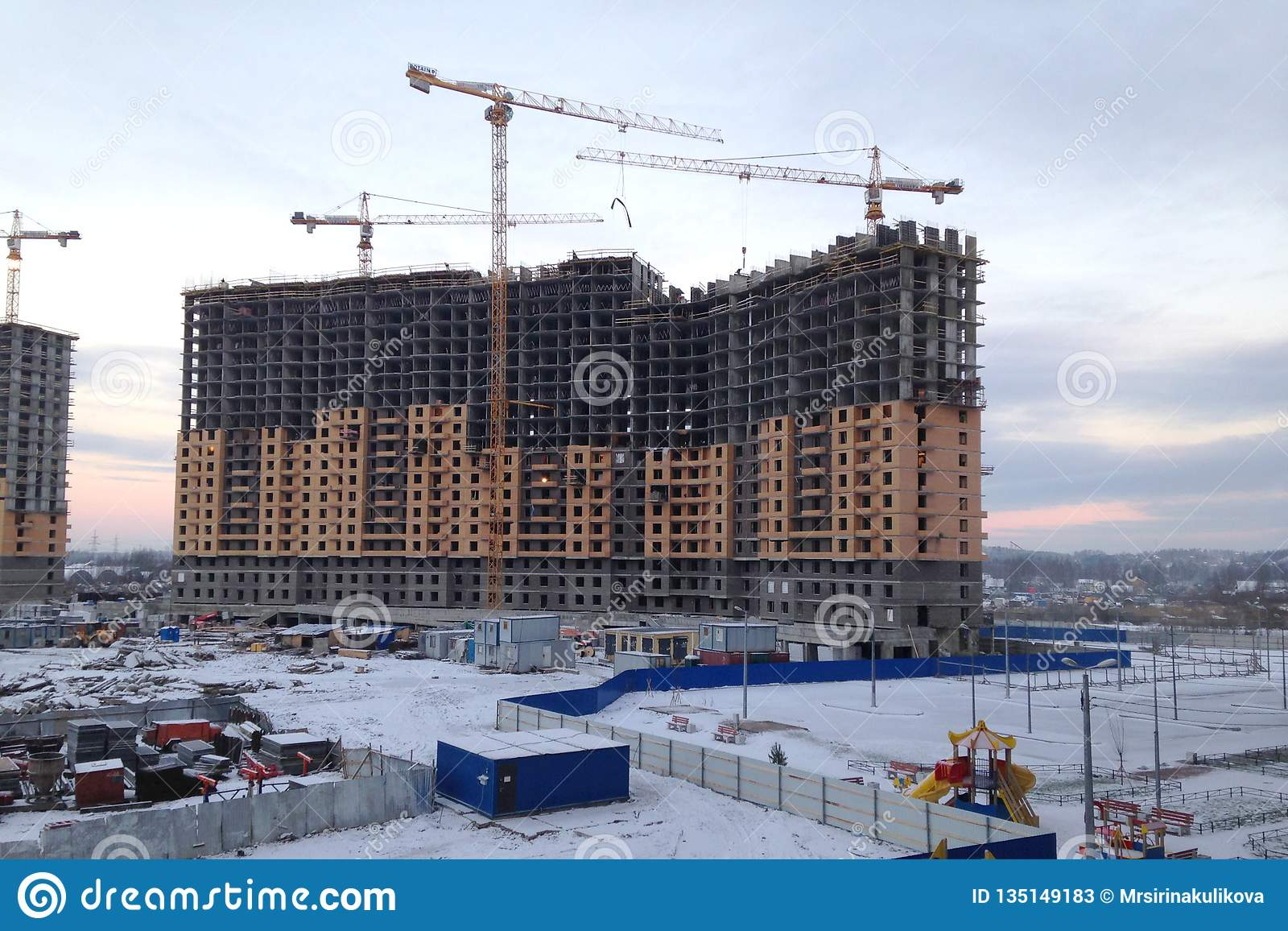 The process of building a large multi-storey residential building in the winter. The work of construction cranes. Half built house