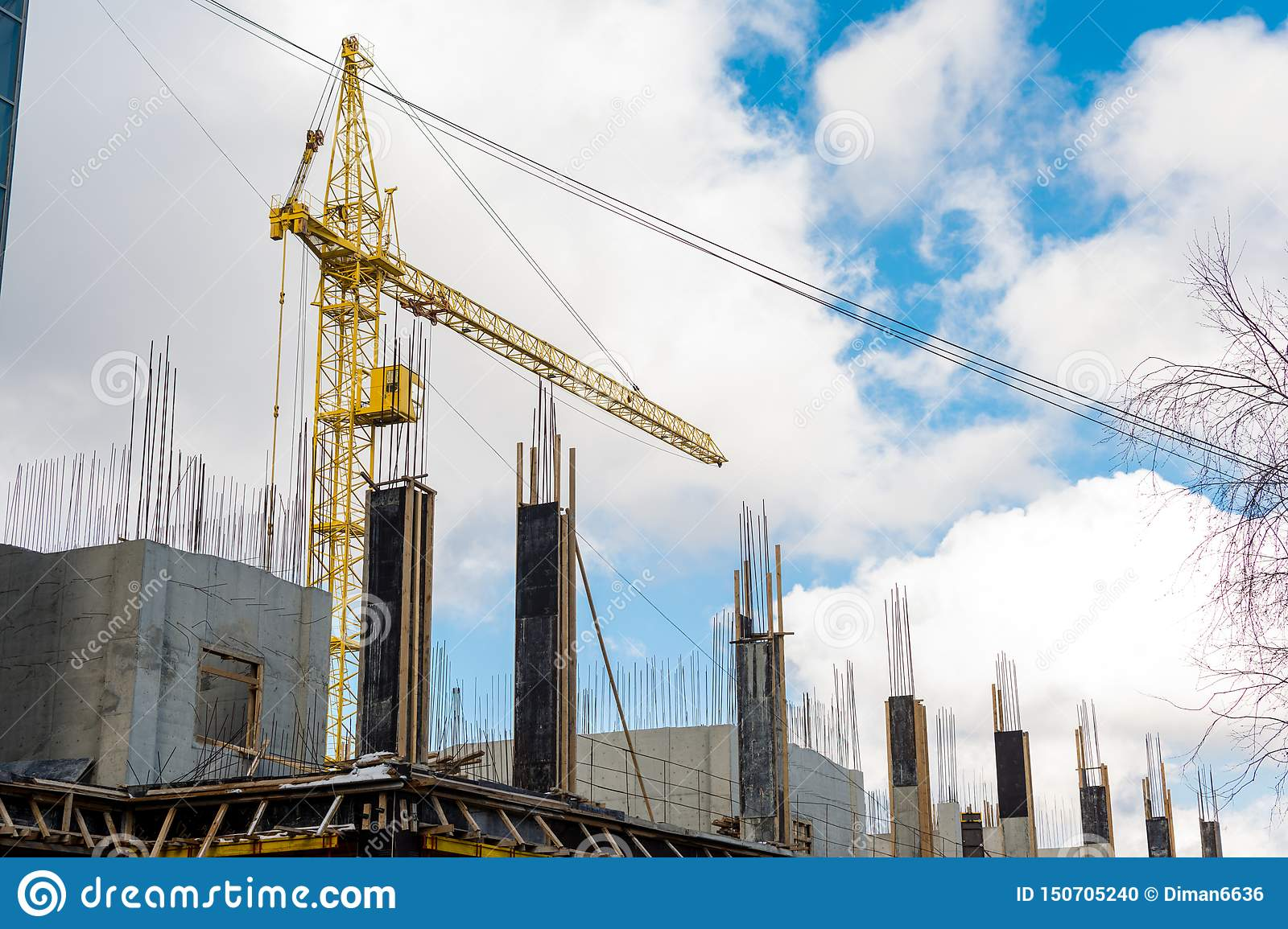 The process of building a multi-storey residential building, a yellow tower crane, poured concrete columns with fittings against a