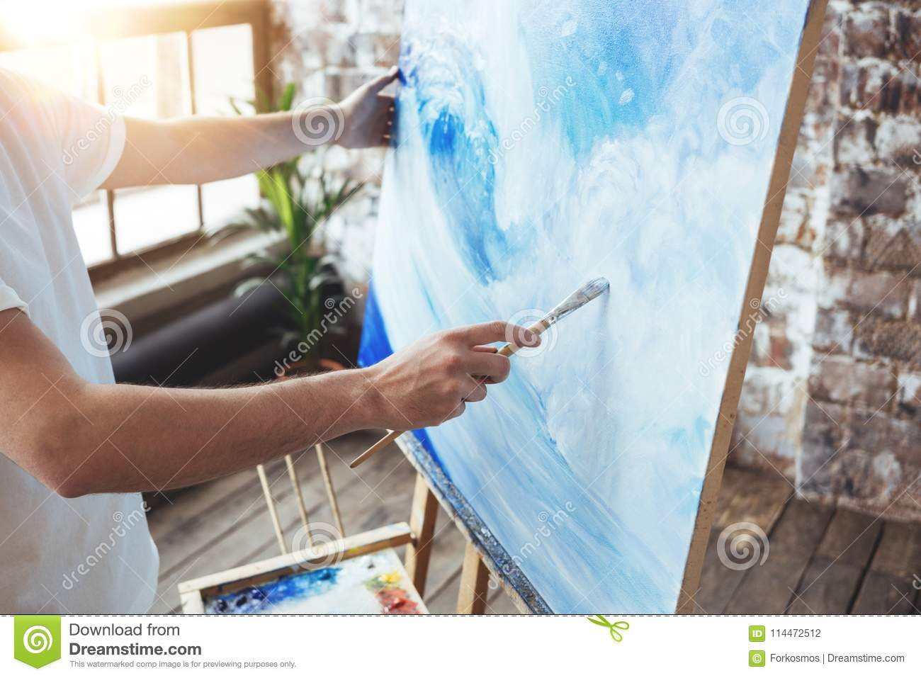 Process of drawing an artist work in art loft studio with oilpaints. Painter hold paintbrush in hand in front of canvas on easel