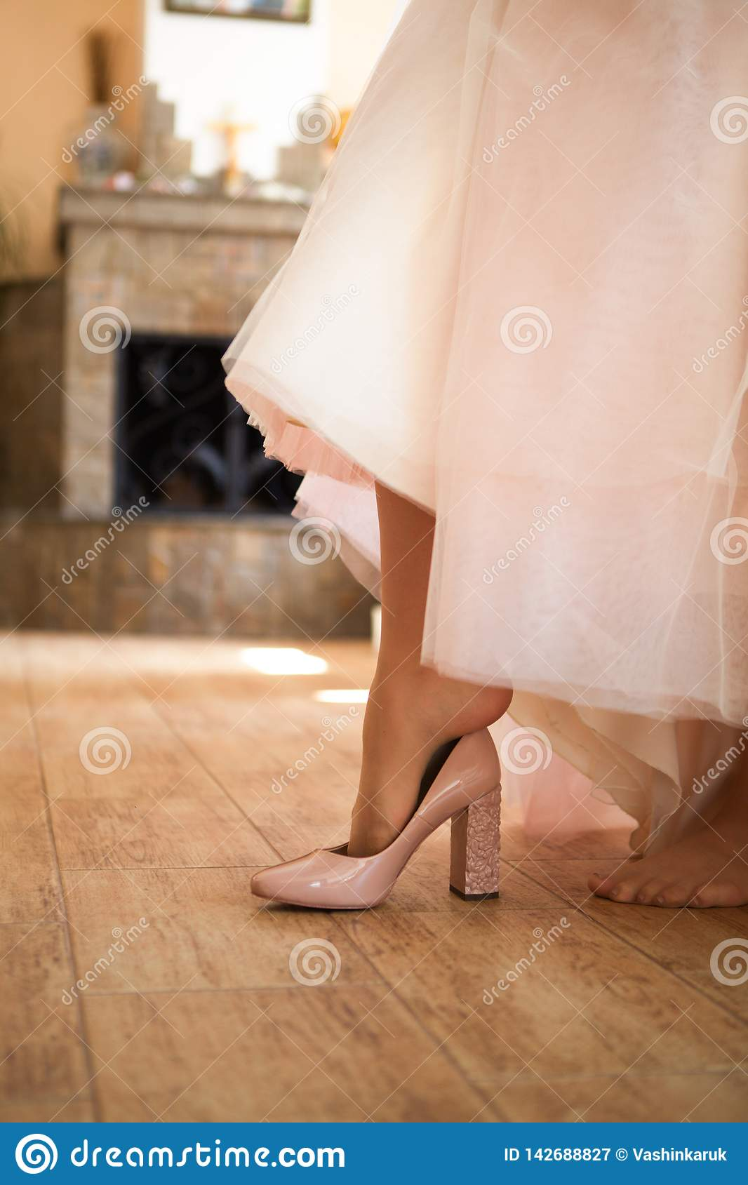 Legs in ivory wedding shoes