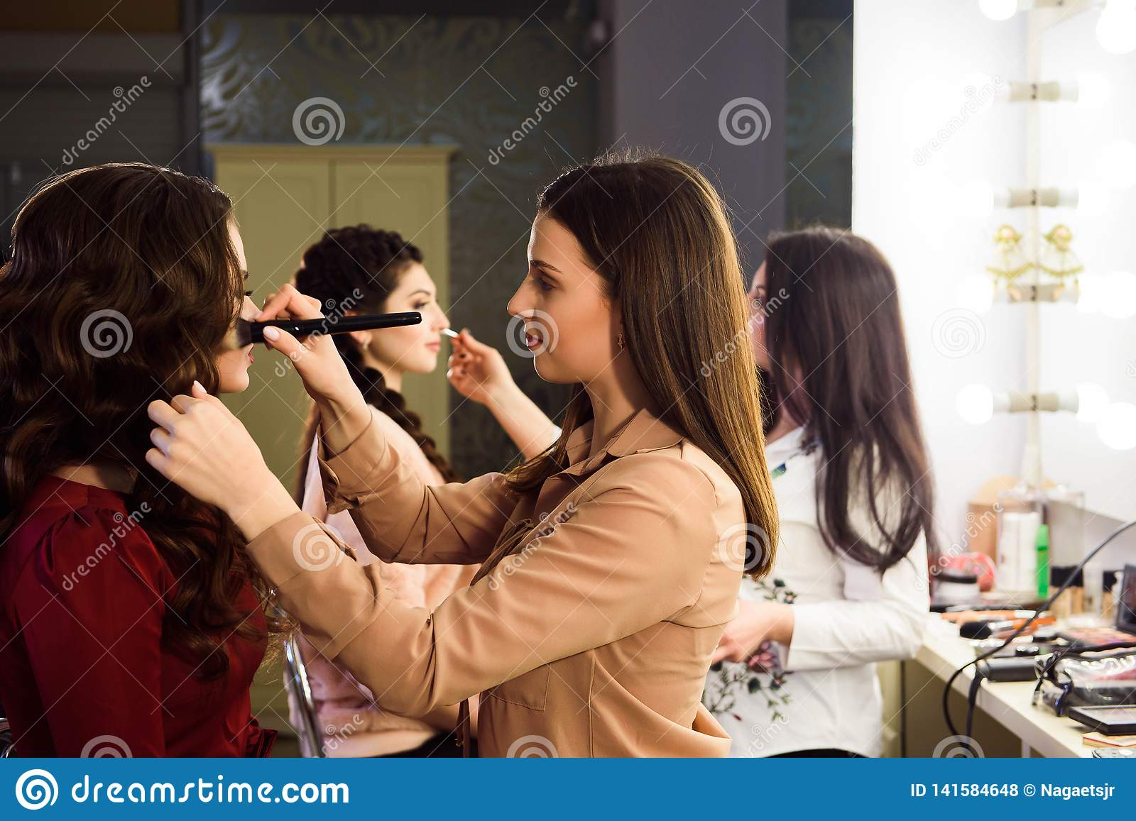 Process of making makeup. Make-up artist working with brush on model face. Portrait of young woman in beauty saloon