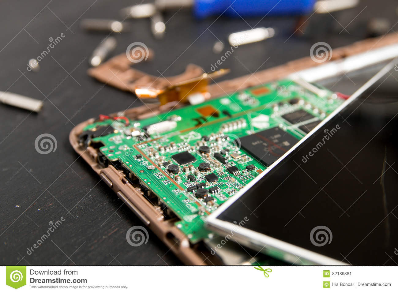 Process of PC Tablet device repair near screwdriver and bit on black wooden background. Disassembled. Broken glass, screen destroy