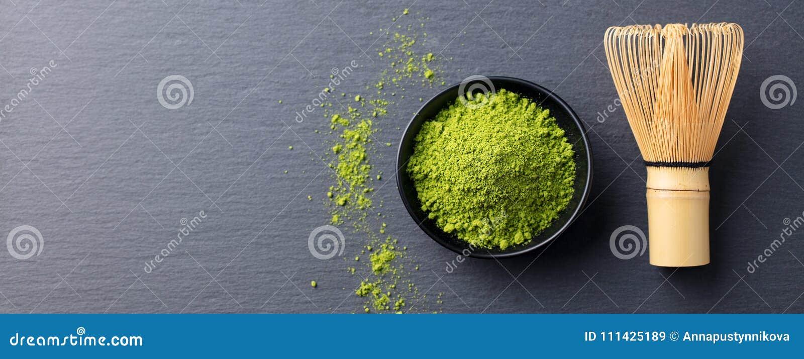 Processo de cozimento do chá verde de Matcha em uma bacia com batedor de ovos de bambu Enegreça o fundo da ardósia Copie o espaço
