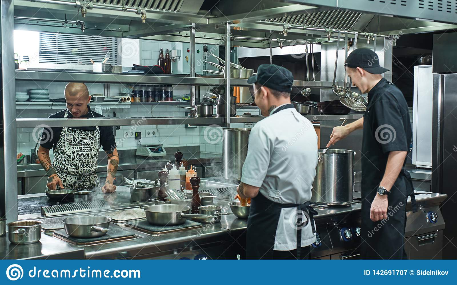 Processo de cozimento Equipe profissional do cozinheiro chefe e do assistente dois novo que preparam o alimento em uma cozinha do