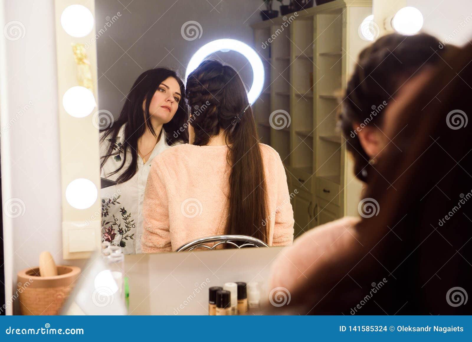 Processus de faire le maquillage Artiste de maquillage travaillant avec la brosse sur le visage modèle Portrait de jeune femme da