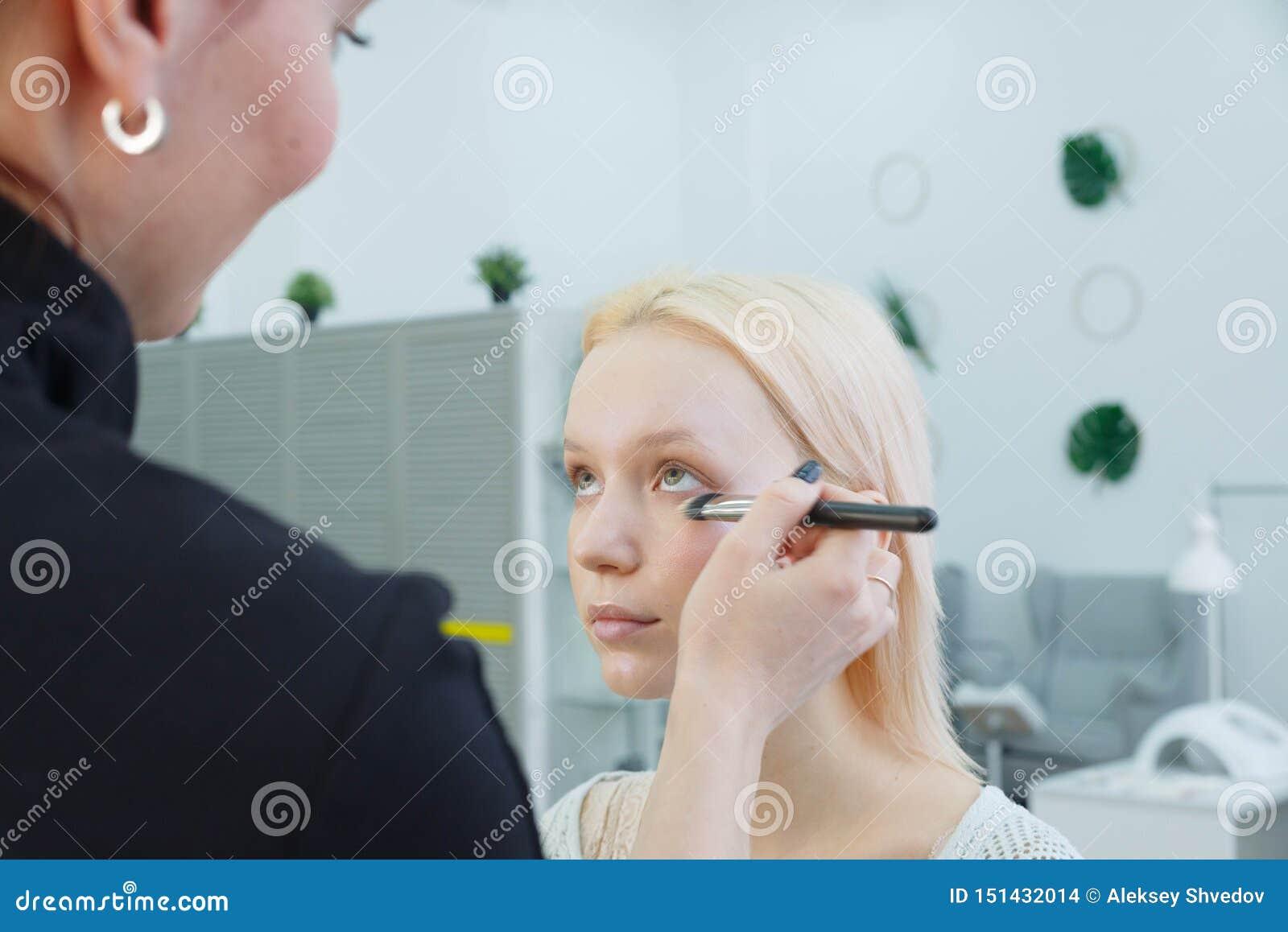 Processus de faire le maquillage Artiste de maquillage travaillant avec la brosse sur le visage mod?le