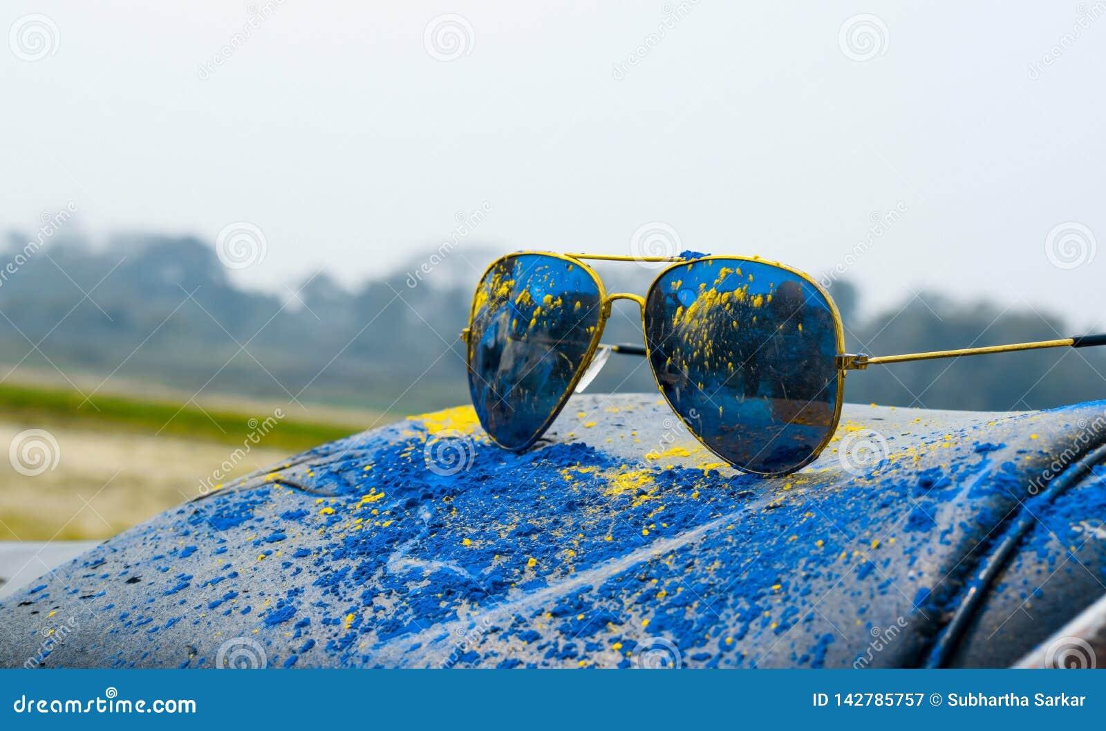 Prochowy błękit i żółty kolor na słońca szkle podczas holi festiwalu