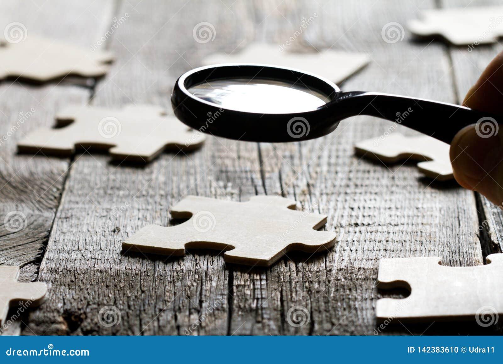 Procurando um sócio do empregado no conceito do negócio com enigma e lente de aumento