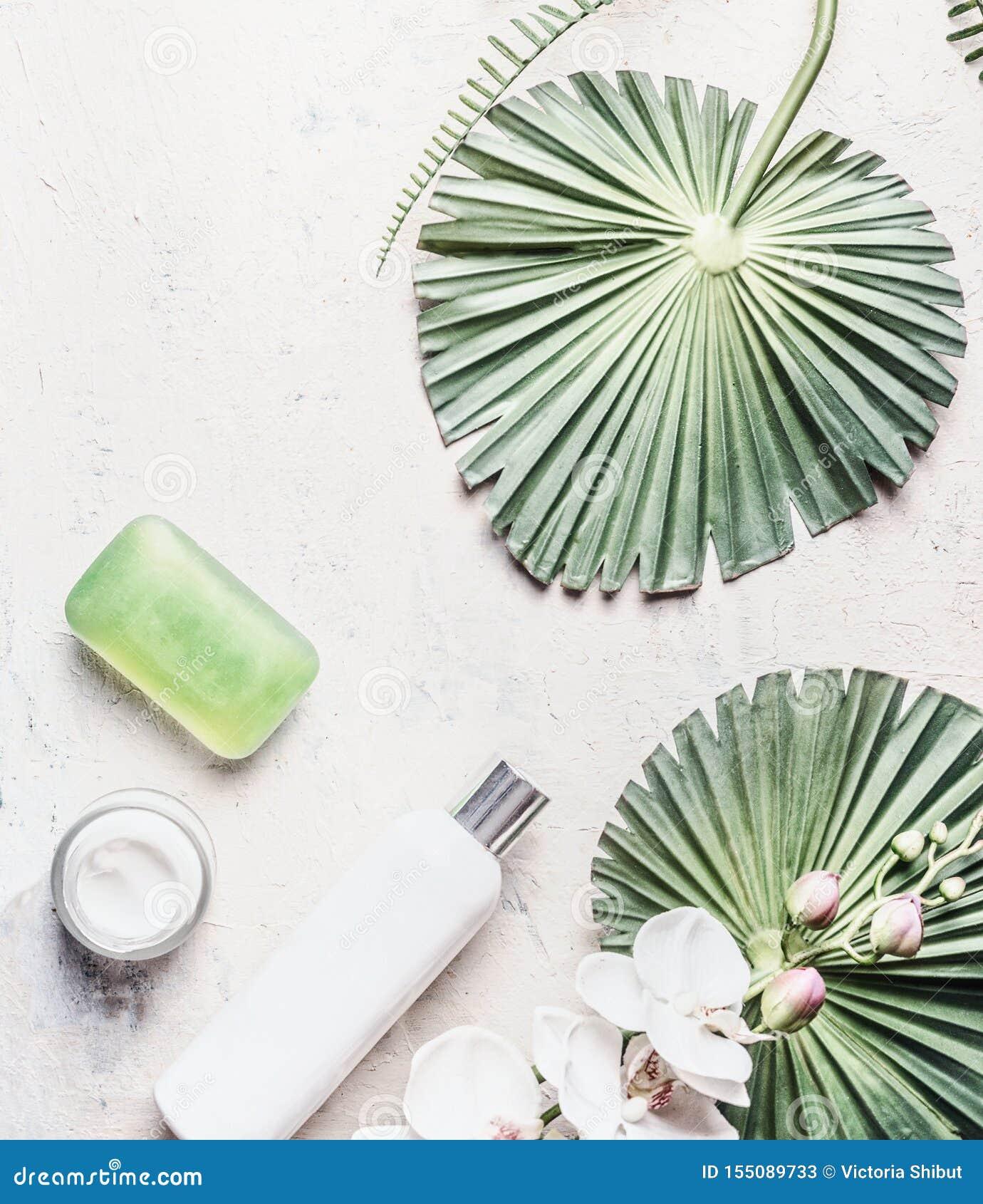 Prodotti di cura di pelle naturali: bottiglie, sapone e crema su fondo leggero con le foglie ed i fiori tropicali, vista superior