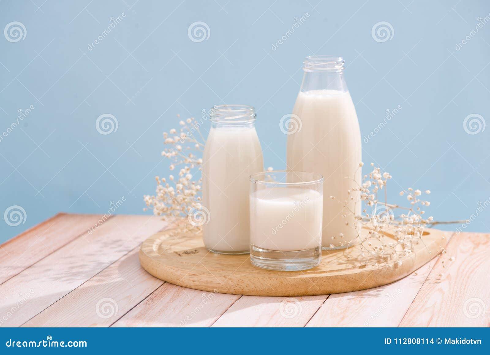 Prodotti lattier-caseario Bottiglia con latte e bicchiere di latte sulla linguetta di legno