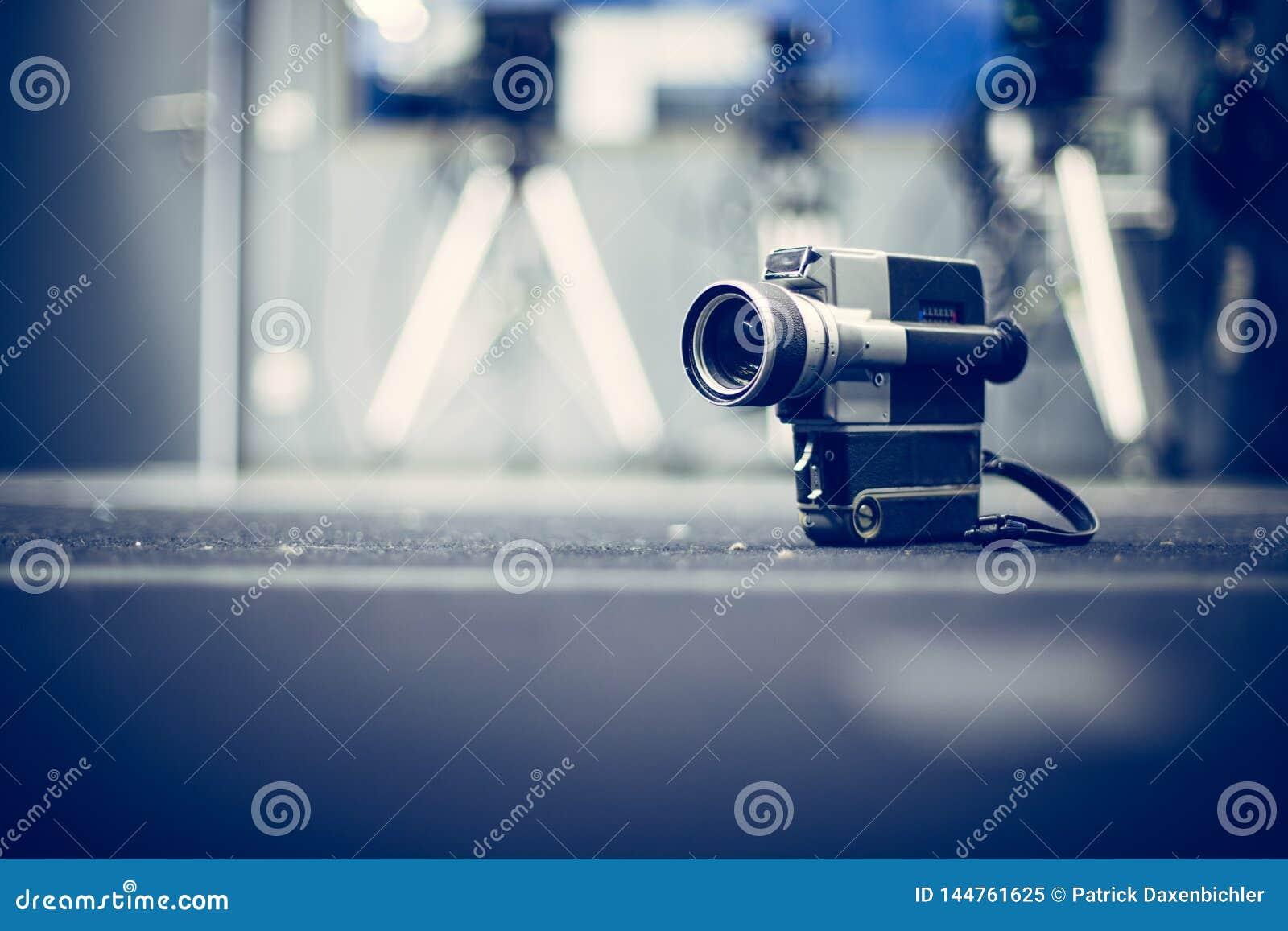 Produção do filme: câmera de filme velha no assoalho, estúdio do vintage da produção no fundo