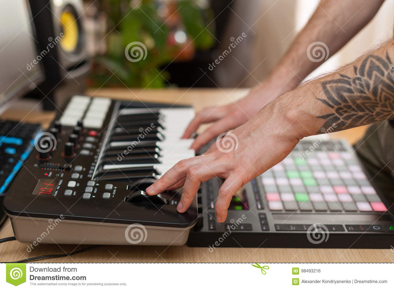 Producer makes a music on MIDI keyboard.