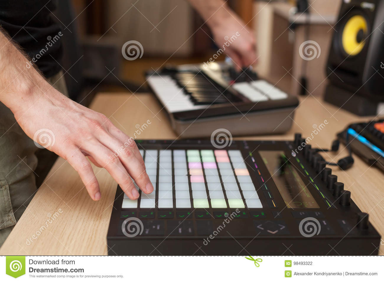 Producer makes a music on professional production controller with push button pads.