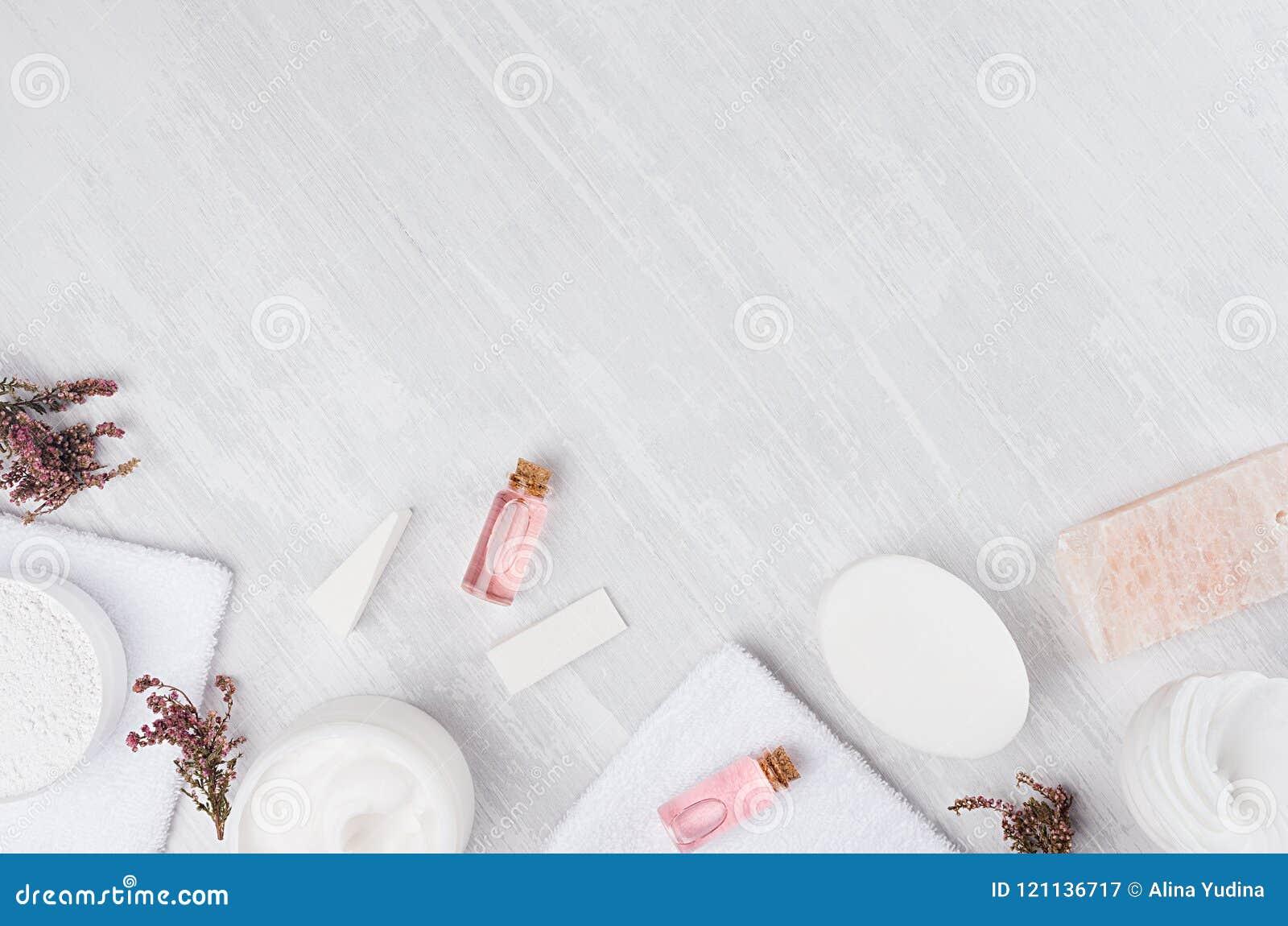 Productos del balneario natural de los cosméticos y accesorios blancos y rosados del baño con las flores rosadas como marco en el