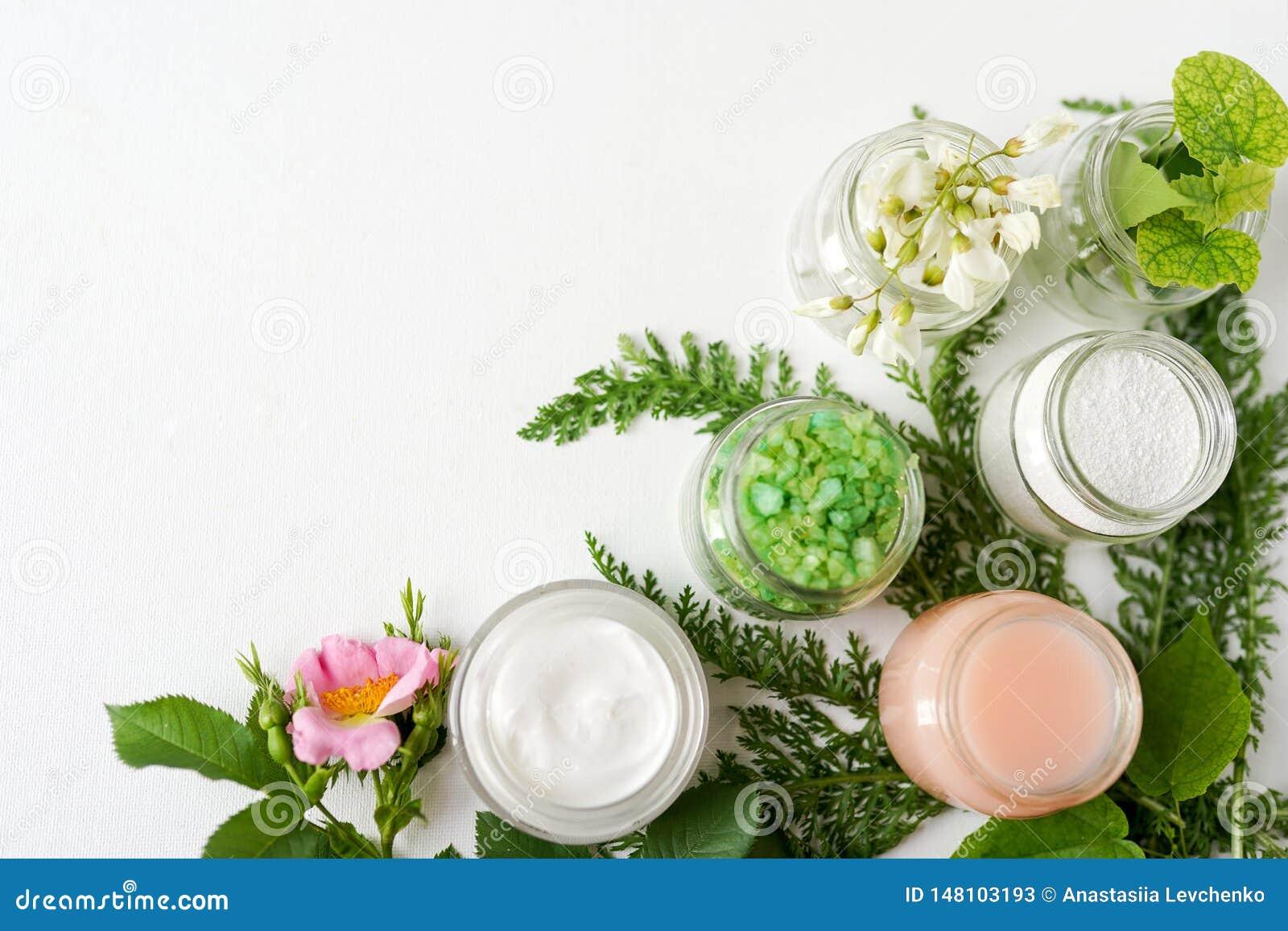 Productos naturales de los cosméticos con las flores y el verdor en el fondo blanco industria de la belleza, espacio de la copia