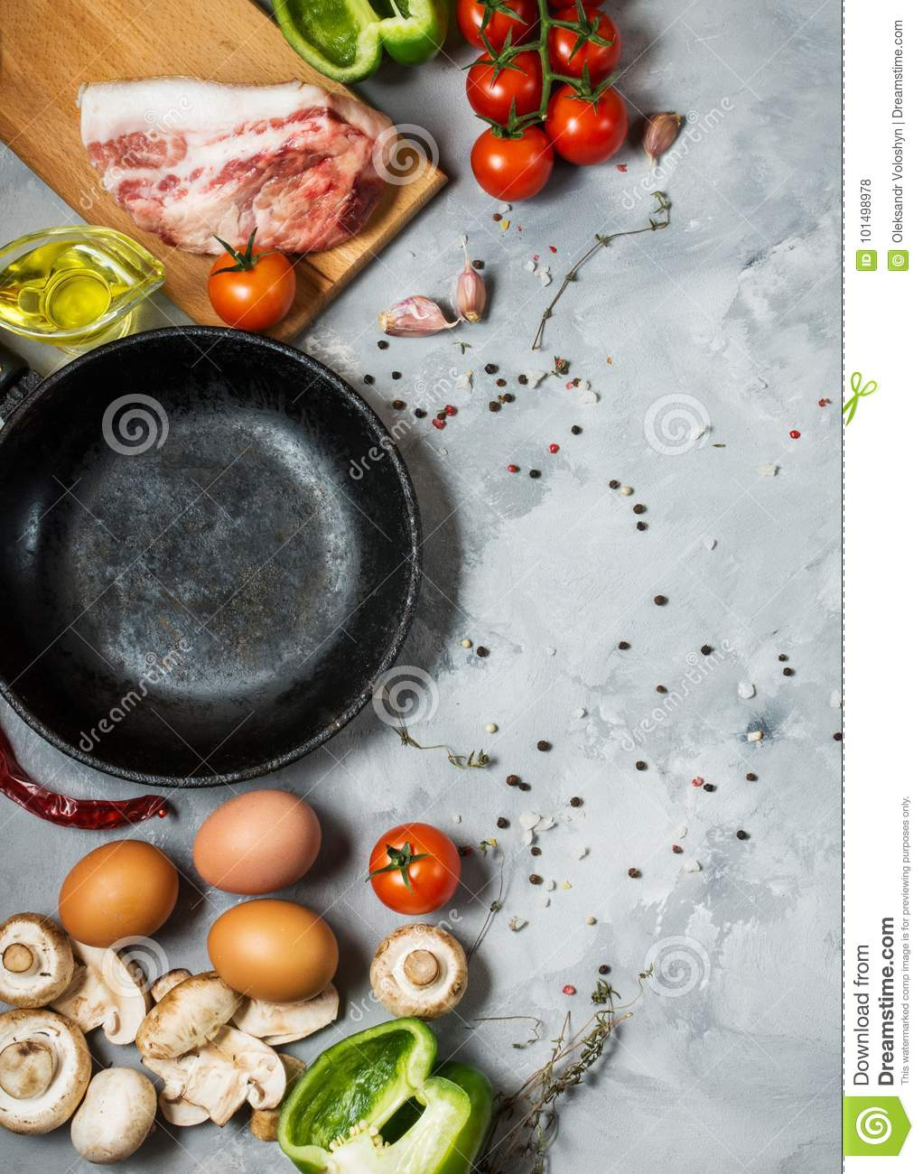 Products for breakfast, eggs, bacon, vegetables, herbs on stone background, top view with copy space.