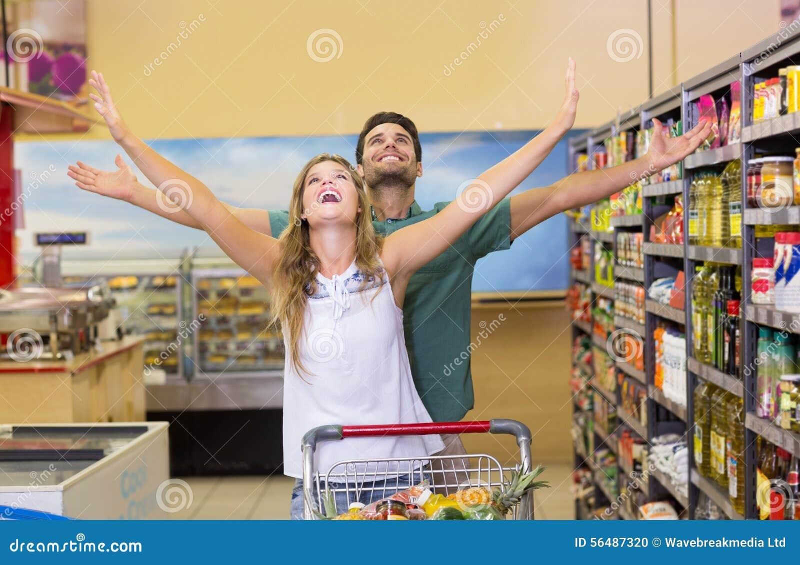 Produits alimentaires de achat de couples lumineux heureux