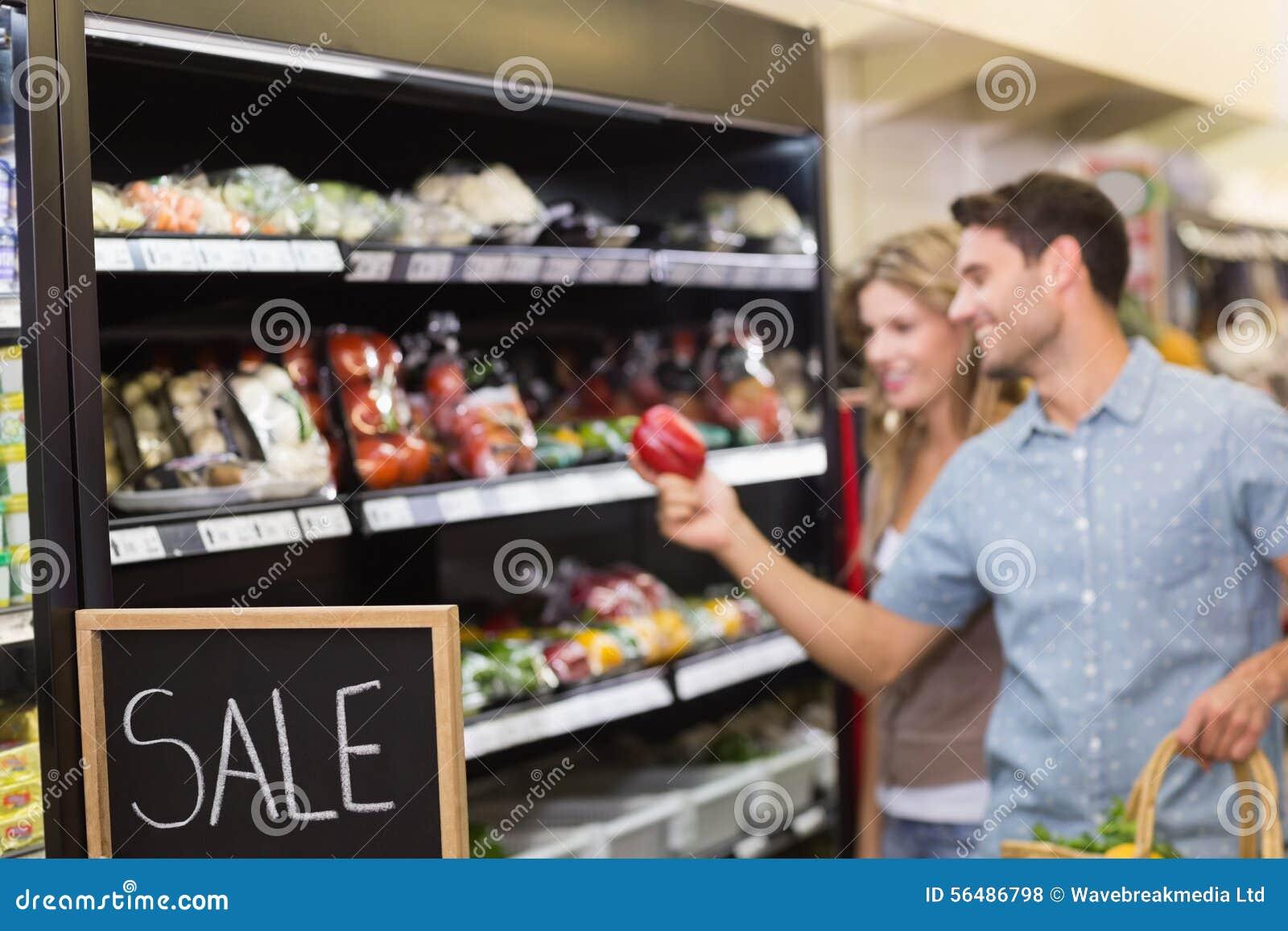 Produits alimentaires de achat de sourire de couples lumineux