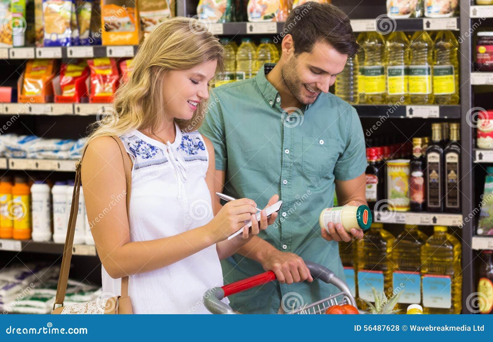 Produits alimentaires de achat de sourire de couples lumineux et inscription sur le carnet