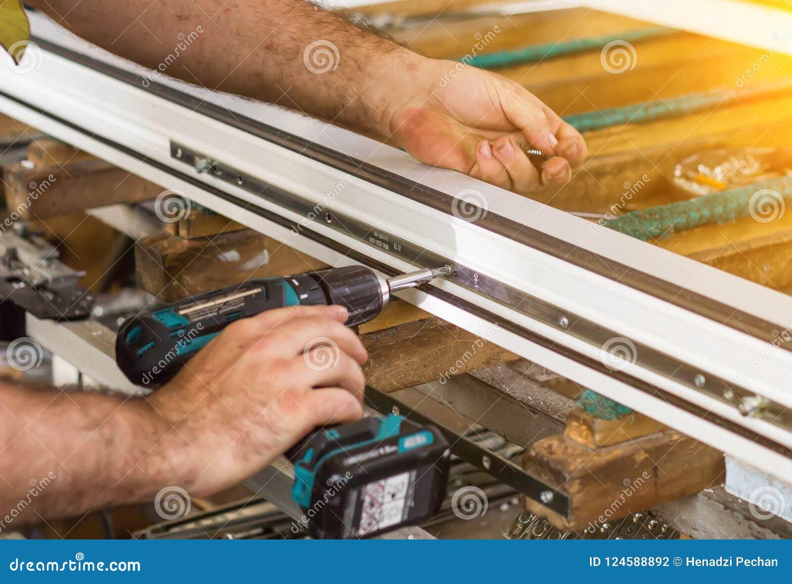 Produktion av pvc-fönster, en man skruvar en skruvmejsel in i ett pvc-fönster, närbilden, fönsterpvc