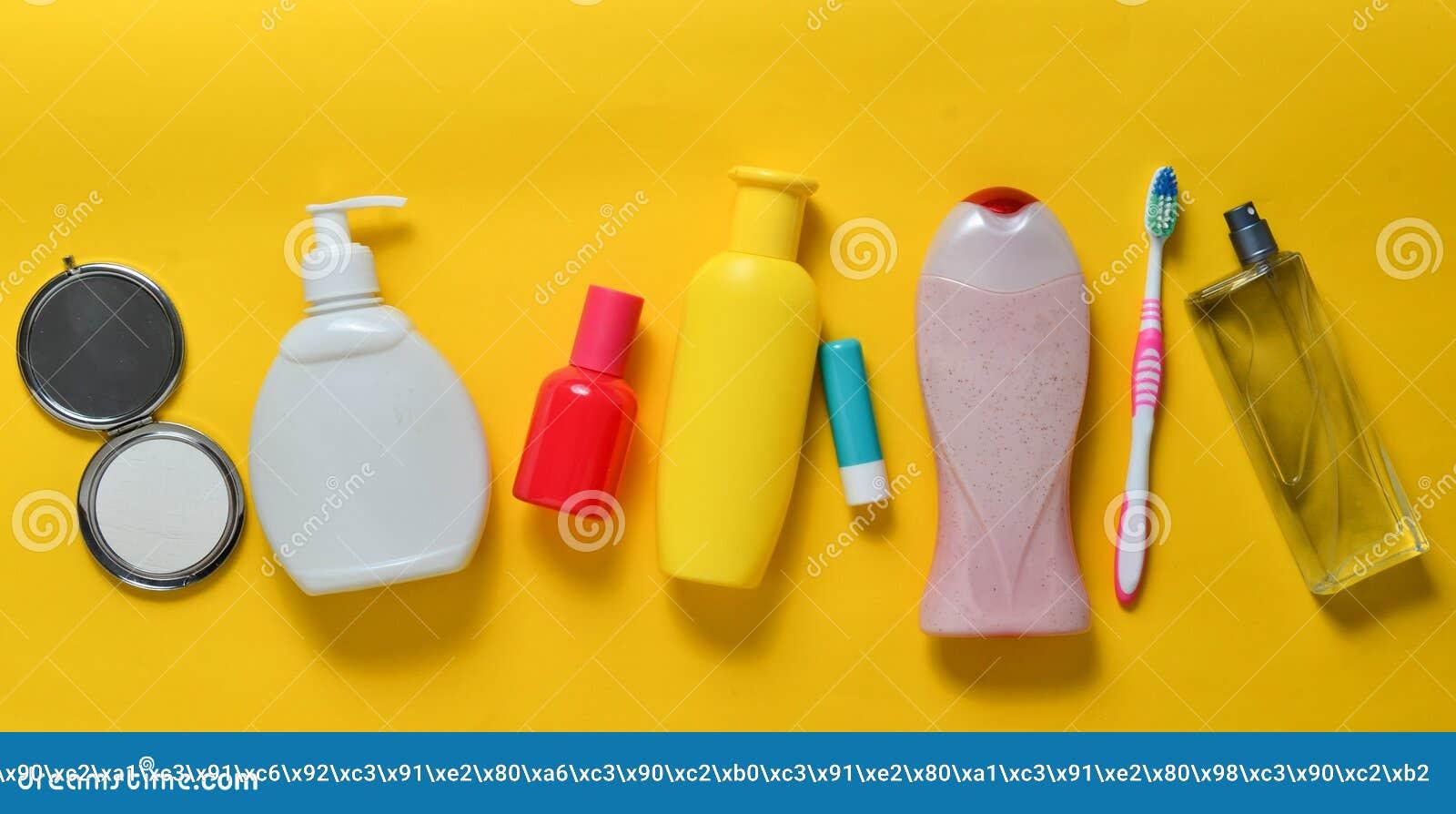 Produkty dla piękna, opieki i higieny na żółtym pastelowym tle, Szampon, pachnidło, pomadka, prysznic gel, toothbrush