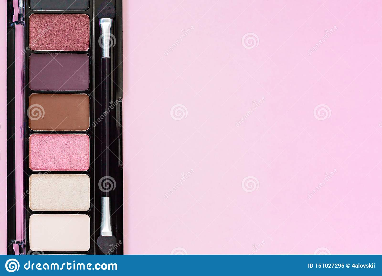 Produtos de composição coloridos da paleta da sombra para os olhos no fundo cor-de-rosa pastel com espaço da cópia