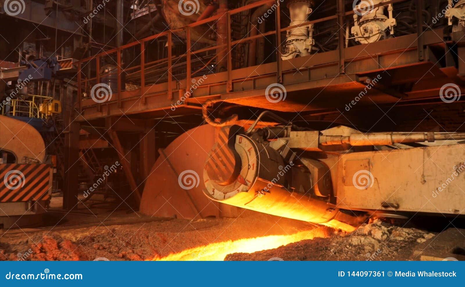 Produzione calda alla fabbrica, concetto del metallo di metallurgia Metraggio di riserva Acciaio fuso che entra nello scivolo met