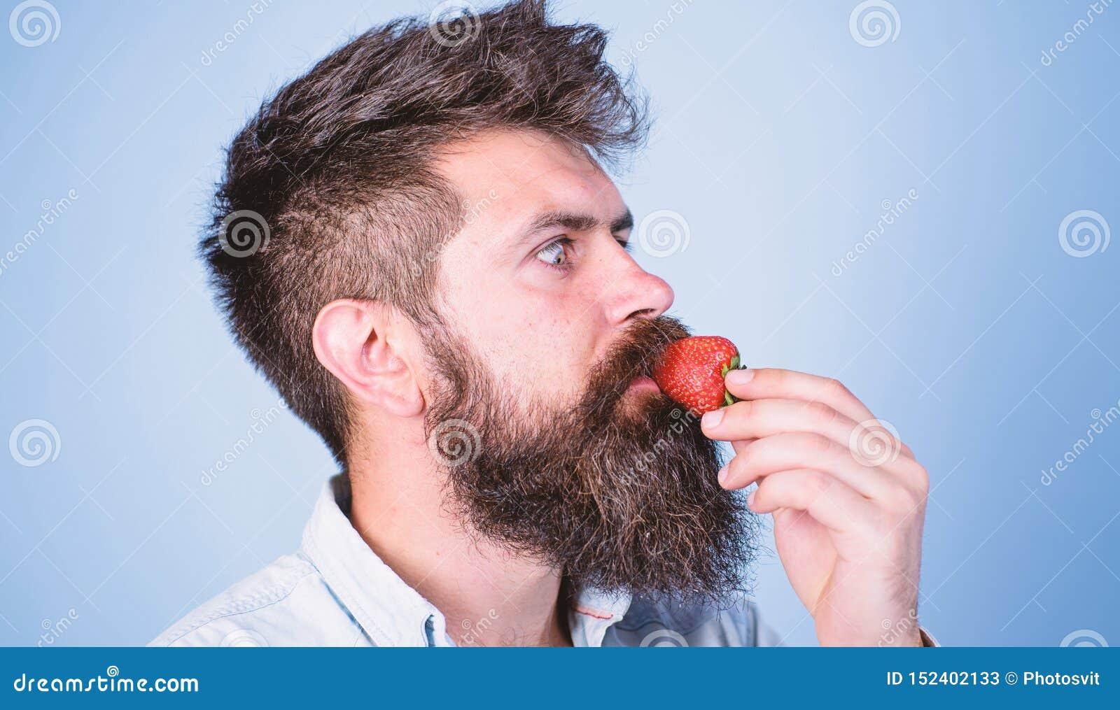 Proeft zo de zomer Aardbei gezonde snack Mensen knappe hipster met lange baard die aardbei eten Bessen