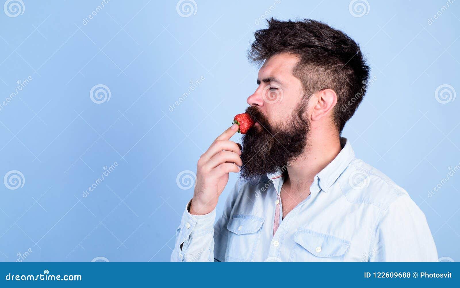 Proeft zo de zomer Mensen knappe hipster met lange baard die aardbei eten Hipster geniet van sappig rijp rood