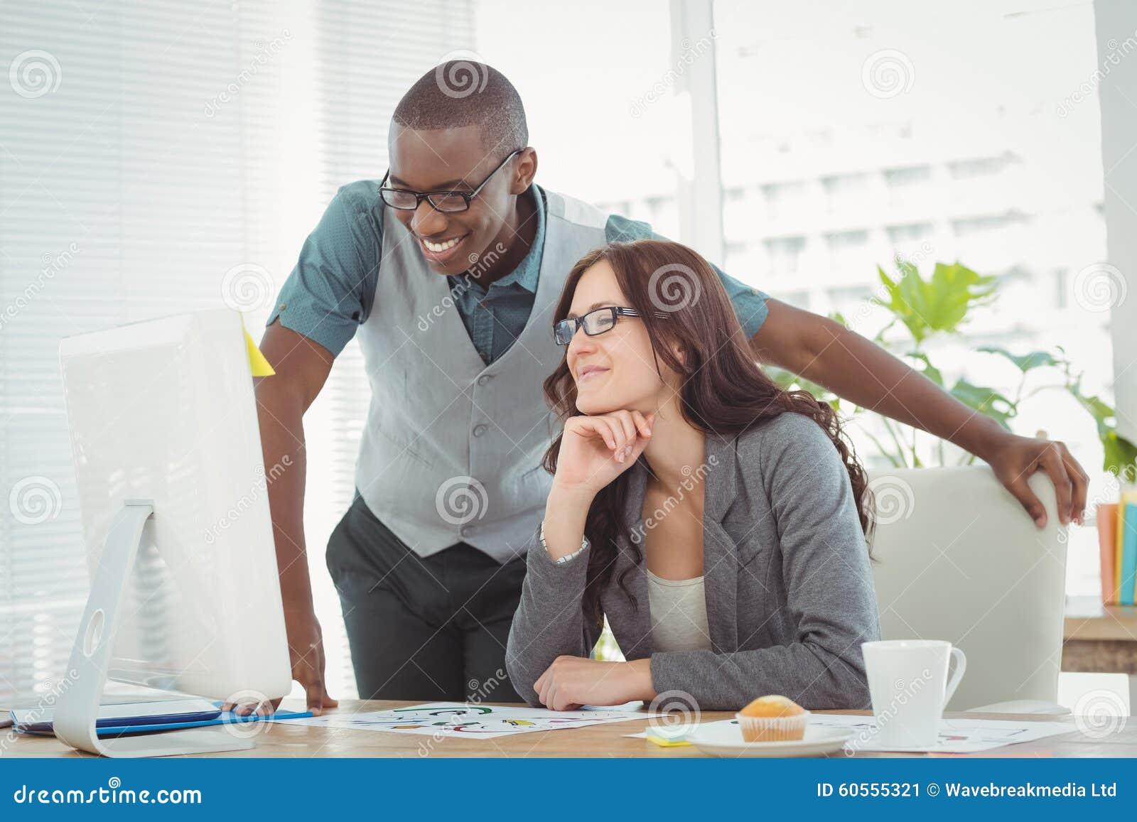 Profesionales sonrientes del negocio que miran el ordenador mientras que trabaja en el escritorio