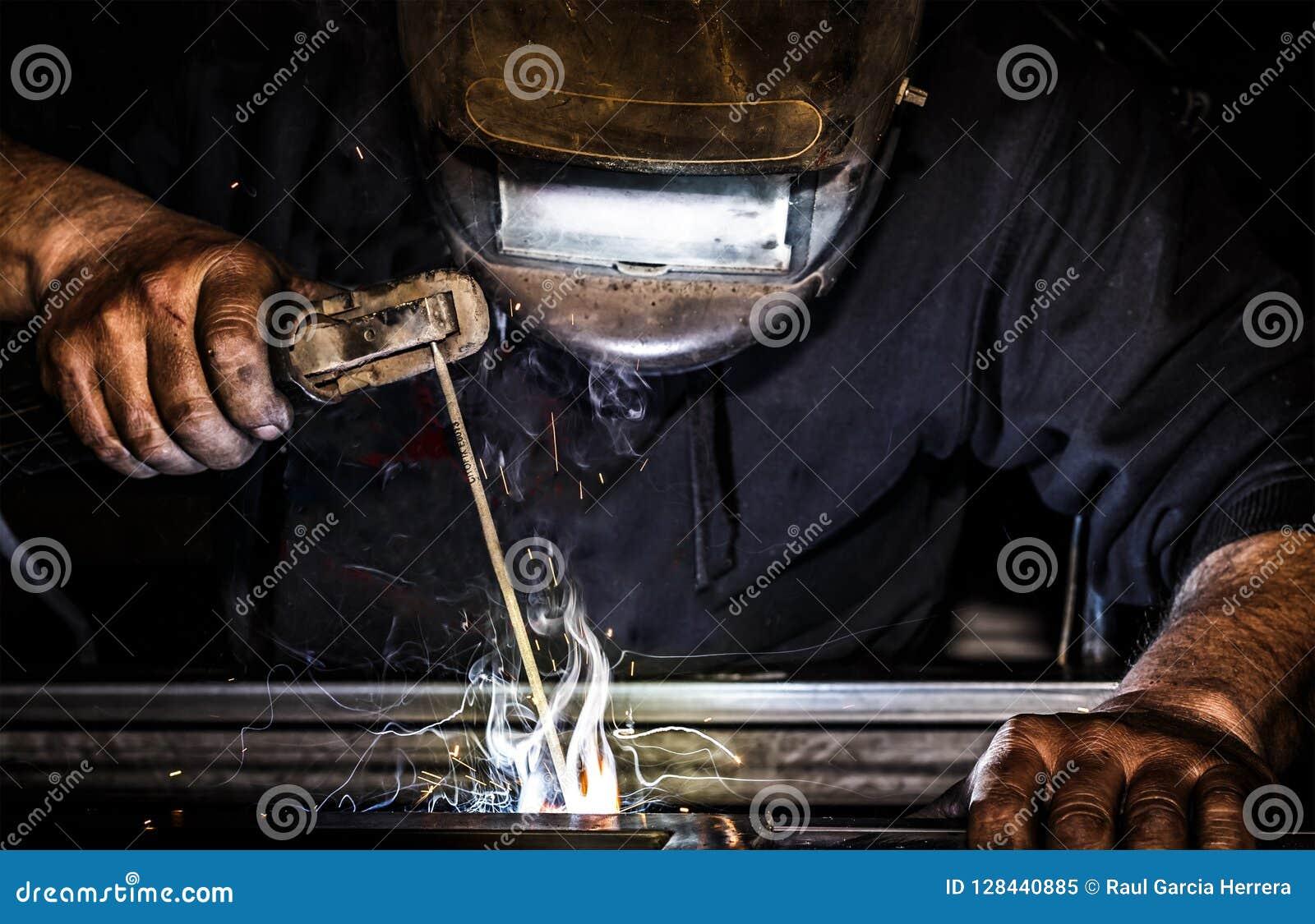 Profesjonalisty spawacza maska ochraniający mężczyzna pracuje na metalu spawie i iskra metalu