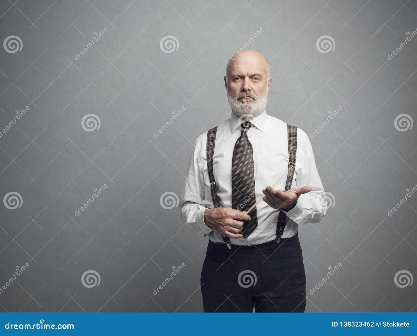 Profesor académico confiado que presenta y que sostiene un palillo