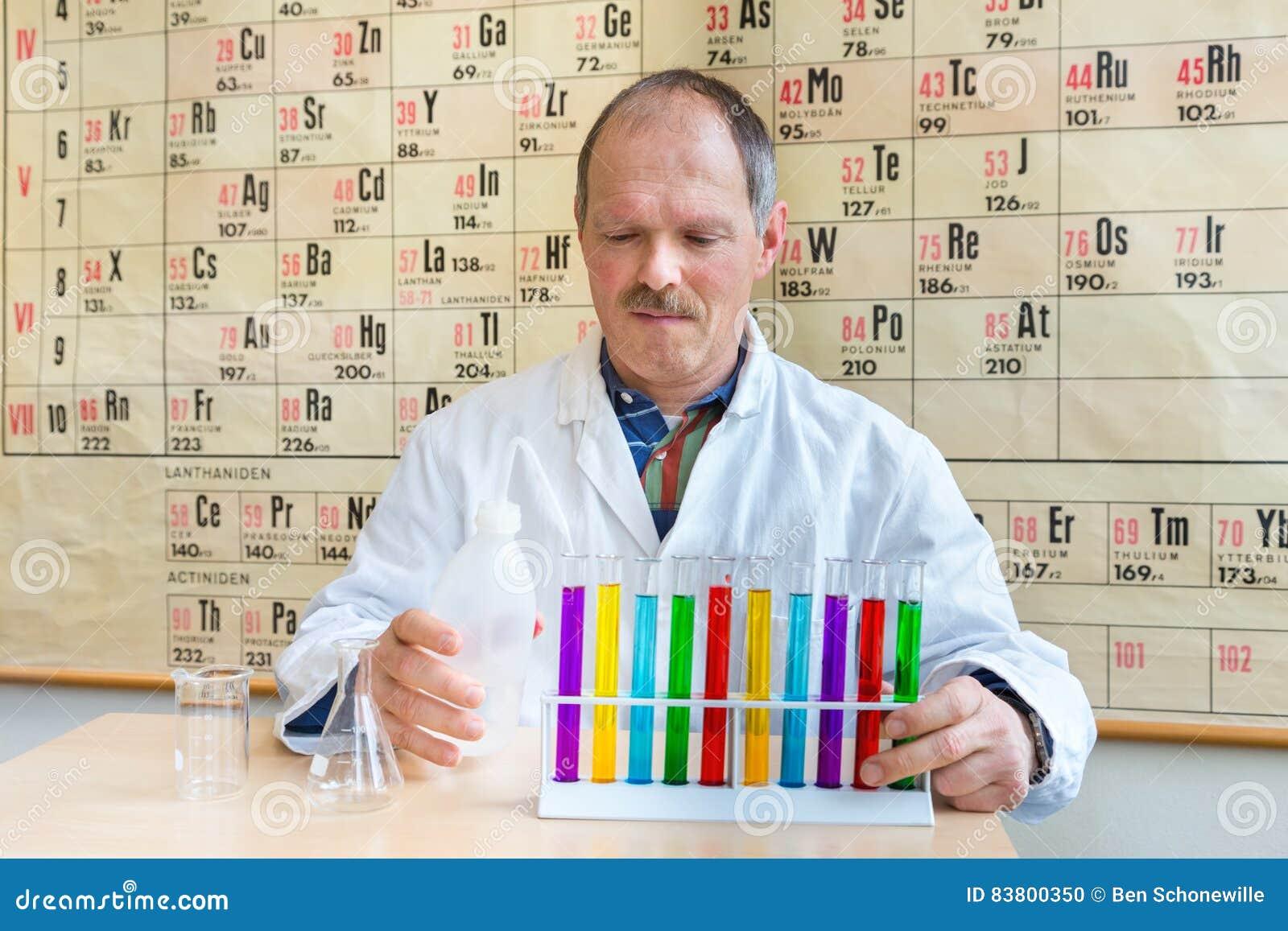 Profesor de la química que llena los tubos de ensayo coloridos