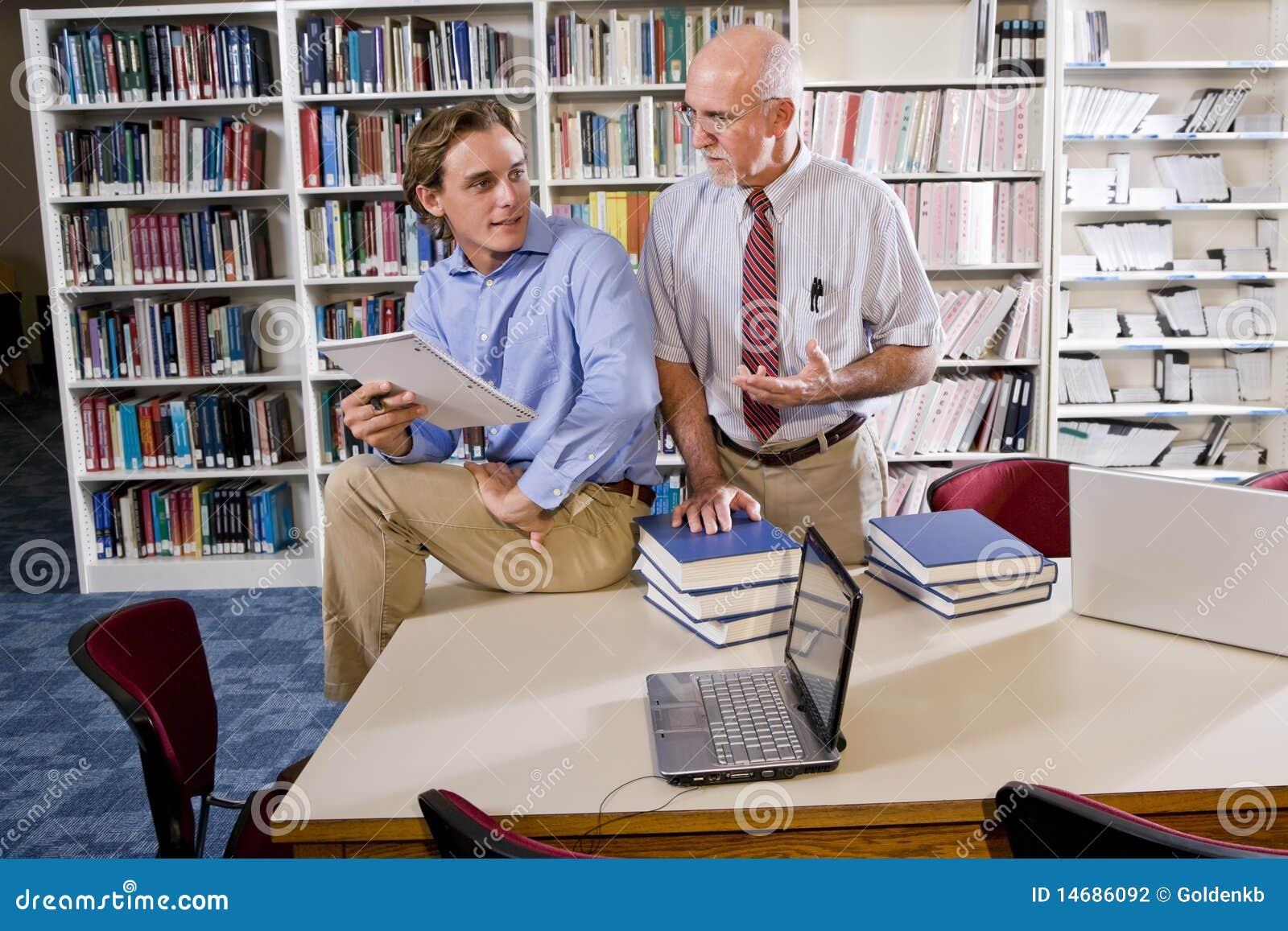 Profesor de la universidad con el estudiante que habla en biblioteca