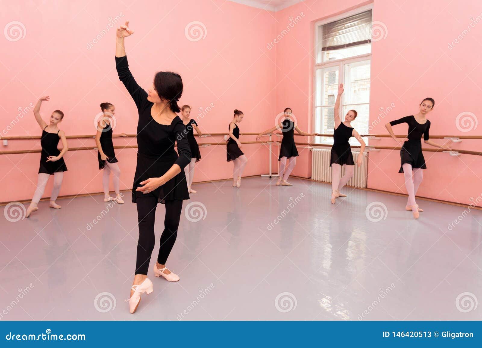 Profesor de sexo femenino maduro del ballet que demuestra movimientos de baile delante de un grupo de adolescentes jovenes