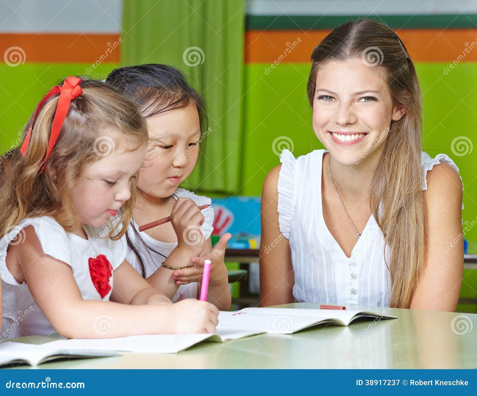 Profesor feliz del cuarto de niños con los niños