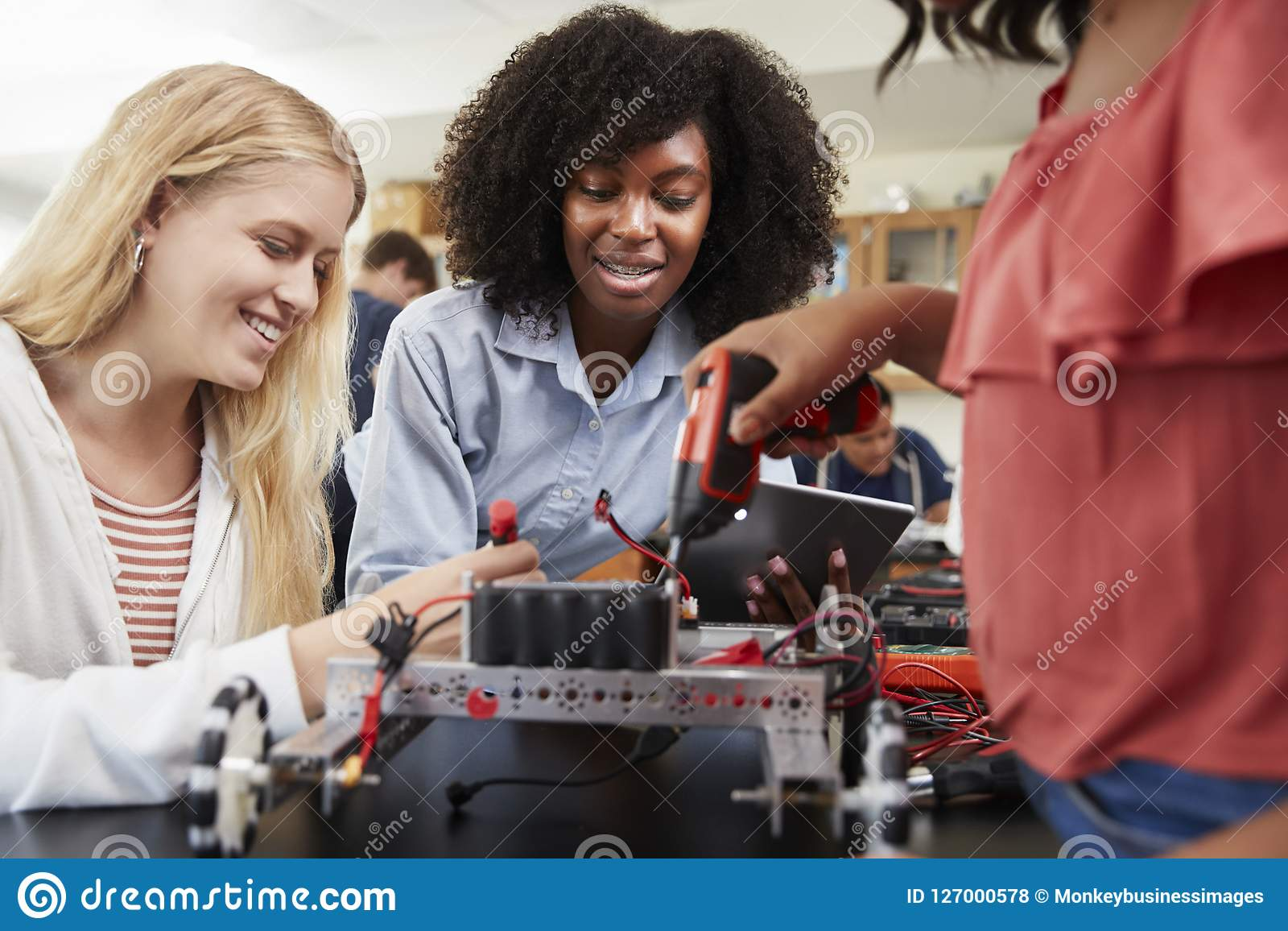 Profesor With Female Pupils que construye el vehículo robótico en la lección de la ciencia