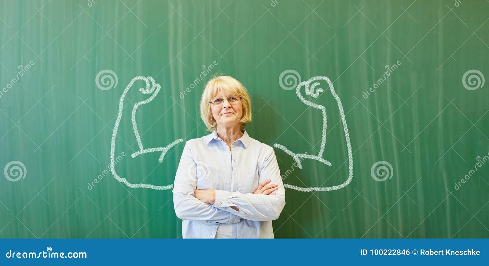 Profesor mayor fuerte con los músculos de la tiza
