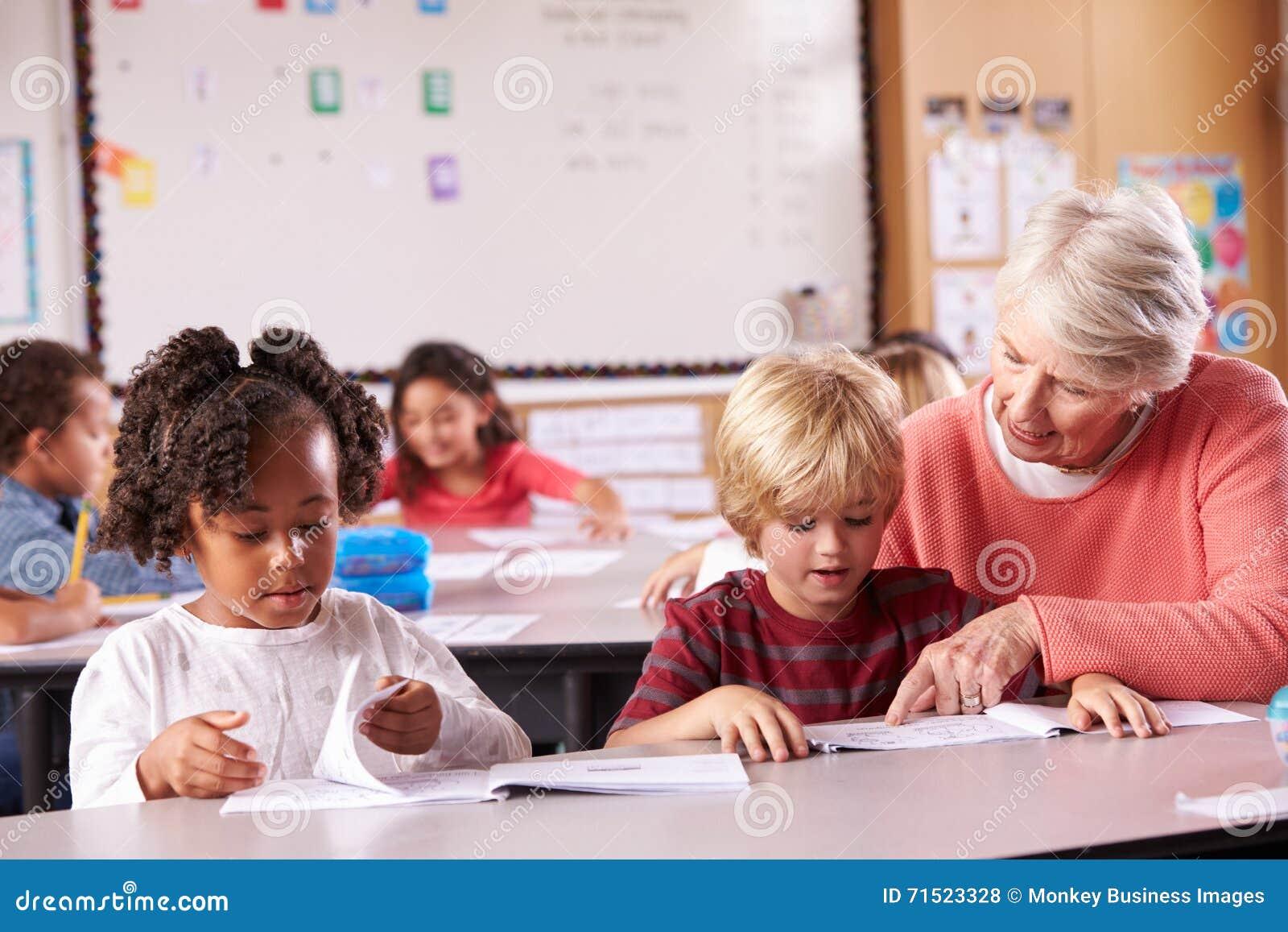 Profesor mayor que ayuda al alumno de la escuela primaria en clase