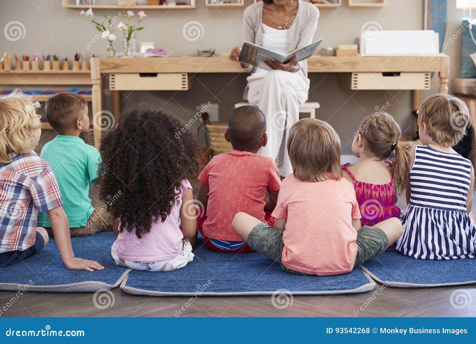 Profesor At Montessori School que lee a los niños en el tiempo de la historia