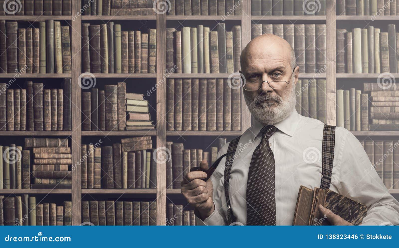 Profesor pozuje w bibliotece z książkami