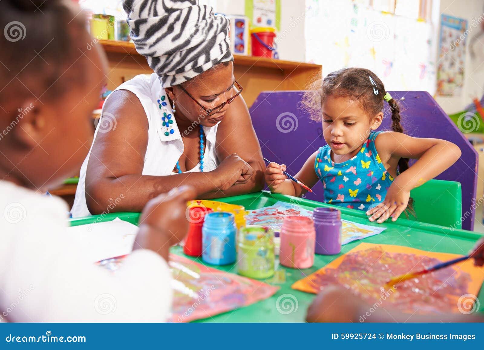 Profesor que se sienta con los niños en una clase preescolar, cierre para arriba