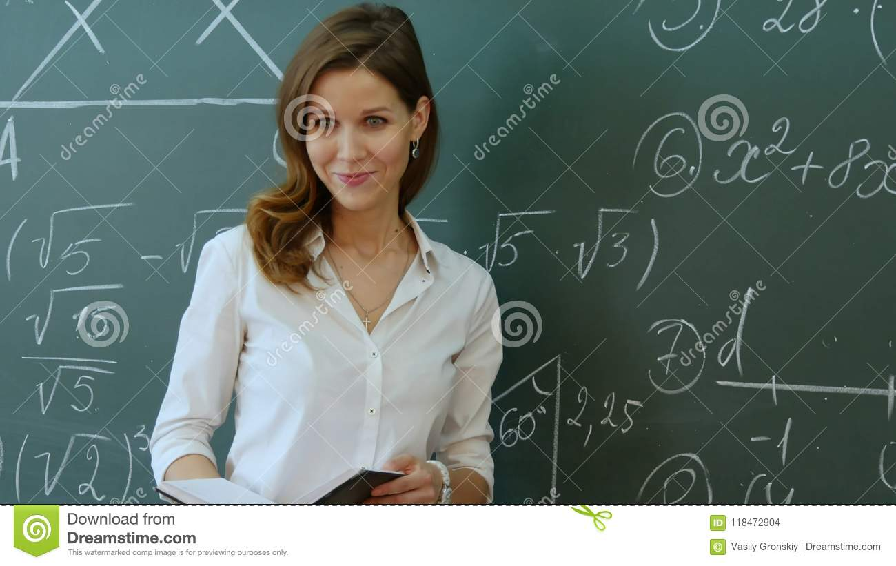 Profesor Standing In Front Of Class Asking Question y sonrisa